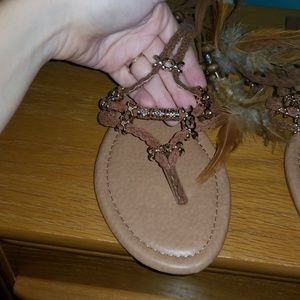 Brown ankle wrap sandals with feather detail.